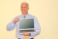 A businessman shows his laptop computer and smiles to the viewer