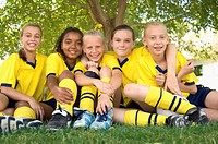 Five girls (10-17) in soccer uniforms sitting on field, portrait