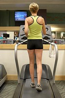 Mature woman running on treadmill, rear view