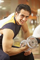 Young man lifting dumbbell in gym, smiling, portrait