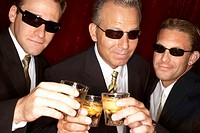 Three men wearing sunglasses, holding glasses of scotch, smiling