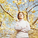 Mature woman standing underneath tree, arms crossed, low angle view