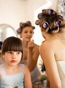 Flower girl (3-5) beside bride applying lipstick in mirror