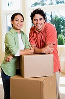 Young couple with cartons in new home, portrait