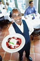 Overhead View of Smiling Waiter Holding Plate of Dessert