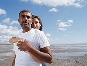 Couple on beach, woman with arms around man