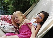 Two girls (6-8) on hammock, smiling, portrait