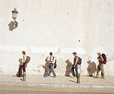 Four men and women wearing rucksacks walking on pavement, side view