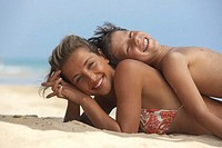 Mother and son (8-10) lying back to back on beach, smiling, portrait