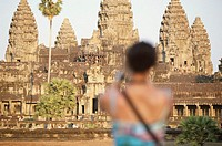 Cambodia, Angkor, woman taking photograph of Angkor Wat temple