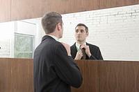 Young businessman adjusting tie in mirror