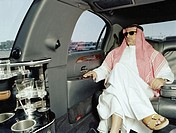 Man in traditional Arabic clothing in limousine