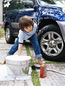Boy (5-7) washing car on driveway plunging hand in bucket
