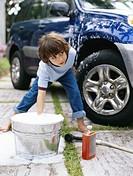 Boy (5-7) washing car on driveway plunging hand in bucket