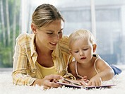 Woman and female toddler (21-24 months) lying on rug, looking at book