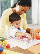Mother at table with son (3-5 years) drawing picture with felt tip pen