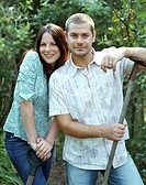 Couple with gardening tools, smiling, portrait