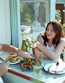Man preparing food for woman at porch table, close-up