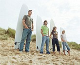 Four friends standing in front of surfboards on beach, low angle view