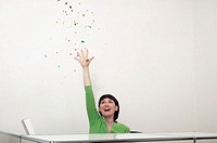 Woman sitting at desk catching confetti, smiling