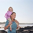 Mother carrying daughter (2-4) on shoulders by beach, smiling