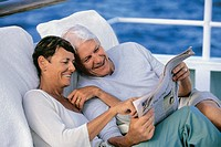 Mature Couple Sit on Sunloungers on Deck of a Boat Reading a Newspaper Together