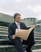 Mature businessman sitting on steps reading newspaper, outdoors
