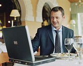 Businessman using laptop at restaurant table