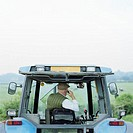 Senior male farmer driving tractor, using mobile phone, rear view