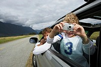 Boy (5-7 years) taking photograph from car window, smiling, portrait