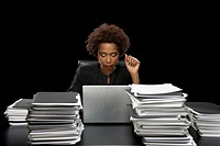 Businesswoman using laptop surrounded by files on desk