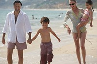 Family walking on beach, father holding son´s (7-9) hand