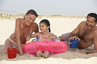 Couple on beach, daughter (2-4) sitting in inflatable ring