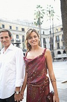 Spain, Barcelona, couple holding hands in Placa Real, portrait