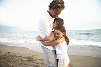 Father embracing son (8-10) and daughter (6-8) on beach