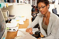 Female office worker wearing earphones and reading document