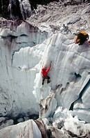 Climber on steep ice face. Fox glacier crevasses near Victoria Falls. Westland National Park. South Island. New Zealand.