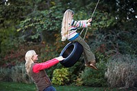 Mother and daughter (7-9) playing on tyre swing, side view
