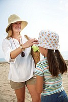 Mother standing on beach adjusting daughter´s (6-8) hat, smiling