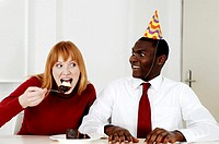 Businessman watching his colleague eating cake