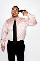 Businessman with cigarette pointing a gun at his head