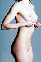 Naked woman cupping her breast.