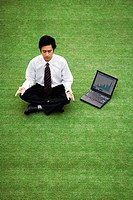 Businessman meditating on the field