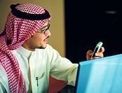 Saudi businessman using mobile phone and laptop