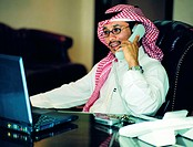 Saudi businessman working on laptop and using telephone