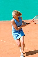 Side View of Female Tennis Player Hitting Ball
