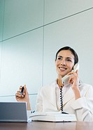 Businesswoman using landline phone