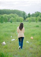 Woman walking in field strewn with plastic bags