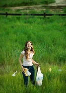 Woman picking up trash in field