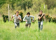 Three young male friends racing across field